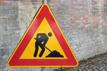 Warning sign showing man digging hole.