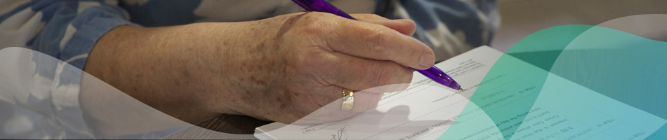Hand holding a pen about to sign a resident's agreement