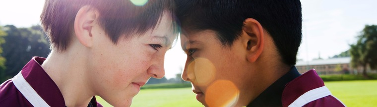 Close-up image of two rugby-playing boys lightheartedly touching heads.