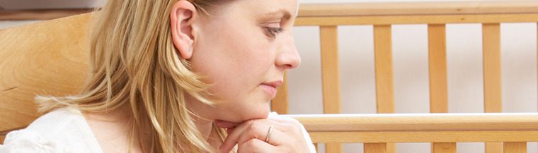 Ectopic pregnancy - woman looking at an empty cot