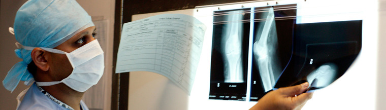 Doctor studying knee replacement X-ray