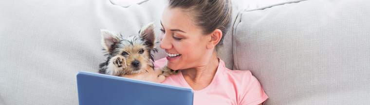 Woman on couch with small dog and ipad