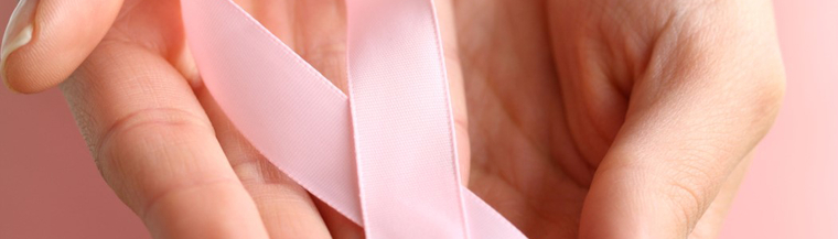 Hand holding a pink ribbon.
