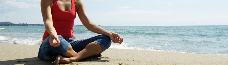 Woman on beach doing yoga for relaxation.