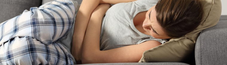 Young woman resting on couch holding stomach due to abdominal pain.