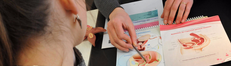 Image of doctor's hands pointing to diagram of the uterus and pelvic floor in front of female patient to illustrate prolapsed uterus.